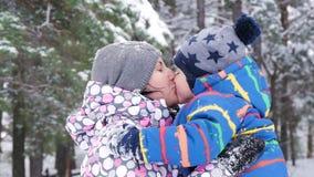 Eine glückliche Mutter umarmt und küsst ihr Kind gegen den Hintergrund eines schneebedeckten Waldes oder des Parks an einem Winte stock footage