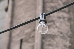 Eine Glühlampe auf einem Draht im Hintergrund einer alten Wand Lizenzfreie Stockfotos