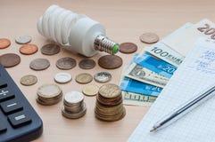 Eine Glühlampe, ein Notizbuch mit einem Stift, Rechnungen, verschiedenes Geld und ein Taschenrechner stockbild