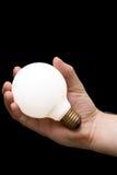 Eine Glühlampe in einer Hand Stockbild