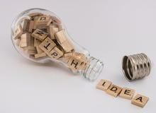 Eine Glühlampe, mit einem abgeschraubten Sockel, füllte mit den Buchstabefliesen und heraus spuckte das Wort ` Idee ` auf einem w Lizenzfreies Stockfoto