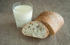 Eine Glasmilch mit Brotscheibe auf einem beige Hintergrund Lizenzfreies Stockfoto