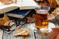Eine Glastasse tee in der Herbstumwelt Lizenzfreies Stockfoto