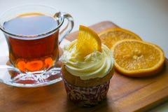 Eine Glastasse tee, ein kleiner Kuchen mit orange Scheiben auf einem hölzernen Behälter stockbild