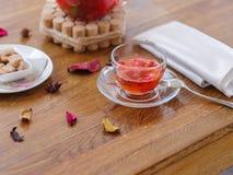 Eine Glastasse tee mit Stücken Erdbeeren und roter Johannisbeere, metallischem Löffel und Serviette auf einem Holztisch Lizenzfreies Stockbild