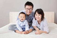 Eine glückliche Familie, die auf weißem Bett sitzt Stockfotografie