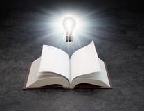 Eine Glühlampe über einem geöffneten Buch Stockfotos