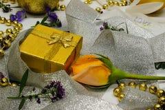 Eine goldene Geschenkbox und eine Rose eingewickelt im silbernen Band Lizenzfreie Stockfotos