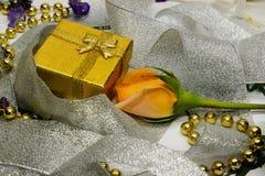 Eine goldene Geschenkbox und eine Rose eingewickelt im silbernen Band Stockfotografie
