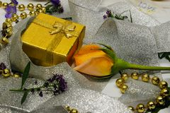 Eine goldene Geschenkbox und eine Rose eingewickelt im silbernen Band Stockbild