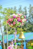 Eine goldene Glocke unter künstlichen Blumen Stockfoto