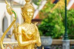 Eine goldene Kinnari-Statue in sawasdee Aktion am Tempel Emerald Buddhas (Wat Phra Kaew) Lizenzfreie Stockfotos