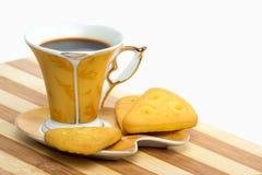 Eine goldene Schale Espresso steht auf einer Untertasse mit einem Plätzchen auf einem weißen Hintergrund Lizenzfreie Stockbilder
