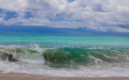 Eine grün-blaue Welle auf dem Strand lizenzfreies stockfoto