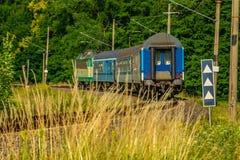 Eine grüne elektrische Lokomotive, welche die tschechische Landschaft führt lizenzfreie stockfotos
