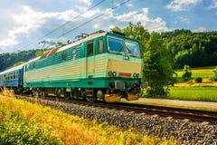 Eine grüne elektrische Lokomotive, welche die tschechische Landschaft führt stockbild