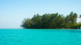 Eine grüne kleine Insel mitten in grünem transparentem Meer stockfotografie