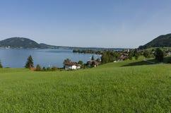 Eine grüne Wiese durch den See mit einem vilage Stockfotos