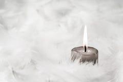 Eine graue brennende Kerze auf weißem Hintergrund mit Federn Stockfoto