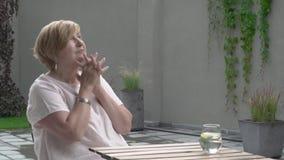 Eine Greisin sitzt draußen und schaut beteiligt Sie schaut besorgt stock video
