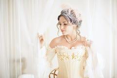 Eine greyhead Frau mit einer schönen luxuriösen Rokokofrisur in einem weißen Kleid, das fertig wird, ein Bad zu nehmen stockfotografie