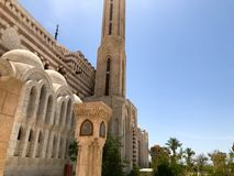 Eine große alte beige arabische islamische moslemische Steinmoschee, ein Tempel für Gebete zu einem Gott mit einem hohen Turm in  lizenzfreies stockbild