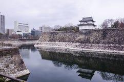 Eine große alte Steinwand und ein kleines Schloss von Osaka ziehen sich zurück Lizenzfreie Stockfotos