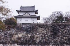 Eine große alte Steinwand und ein kleines Schloss von Osaka ziehen sich zurück Lizenzfreies Stockbild