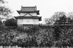 Eine große alte Steinwand und ein kleines Schloss von Osaka ziehen sich zurück Stockfotografie