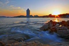 Eine große Ansicht von Meer, von Felsen, von Gebäude und von Sonnenuntergang Stockfotografie