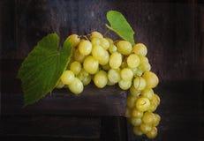 Eine große Bürste von grünen Trauben mit Blättern auf einem hölzernen Hintergrund in der rustikalen Art Stockfotografie