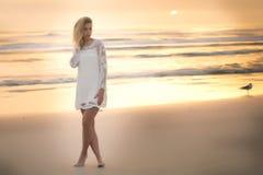 Eine große blonde Frau, die auf den Strand bei Sonnenaufgang geht Lizenzfreies Stockbild