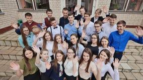 Eine große Firma von den glücklichen Studenten, die ihre Hände auf den Schritten ihrer Schule wellenartig bewegen lizenzfreies stockbild