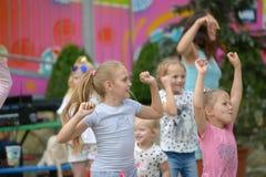 Eine große Gruppe des glücklichem Spaßsportkinderspringens, -sport und -tanzen Kindheit, Freiheit, Glück, das Konzept von einem a stockfotografie