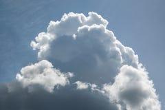 Eine große Kumuluswolke in einem blauen Himmel mit Federwolkewolken Stockfotos