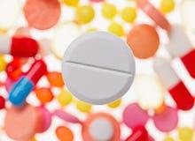 Eine große Makroansicht der Tablette (Pille) über unscharfe mehrfarbige Drogen Stockbild