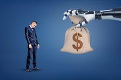 Eine große Roboterhand gibt einem kleinen traurigen Geschäftsmann eine große Geldtasche mit einem Dollarzeichen stockbilder