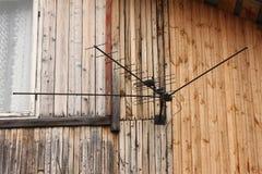 Eine große schwarze Antenne mit einem Draht auf der Wand eines Wohnhauses mit einem weißen Fenster Stockfotografie