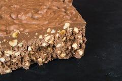 Eine große Stange der Milchschokolade mit Nüssen und airbubbles Lizenzfreie Stockfotos
