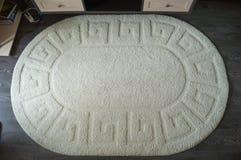 Eine große weiße ovale Wolldecke auf einem dunklen Laminat Lizenzfreies Stockfoto