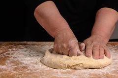 Eine Großmutter der alten Frau knetet einen Teig für das Kochen des Brotes lizenzfreies stockbild