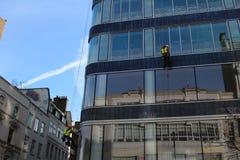 Eine Gruppe Arbeitskräfte, die waschende Fenster auf hohem Aufstiegsgebäude säubern stockfotografie