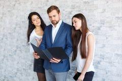 Eine Gruppe Büroangestellte, Gleicher in einen schwarzen Ordner mit Dokumenten Stockbild