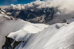 Eine Gruppe Bergsteiger, die auf einen Gebirgsrücken über der Klippe gehen Stockfotografie