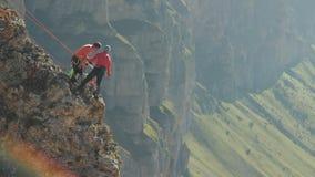 Eine Gruppe Bergsteiger, die einen Aktionsplan stehend am Rand der Klippe besprechen stock video
