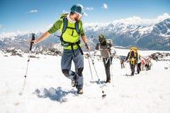Eine Gruppe Bergsteiger klettert zur Spitze eines Schnee-mit einer Kappe bedeckten Berges Stockfotos