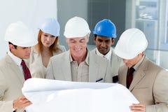 Eine Gruppe des Architekten ein Projekt behandelnd Stockbilder
