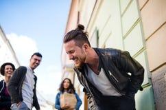 Eine Gruppe des jungen Freundgehens im Freien in der Stadt, Spaß habend lizenzfreie stockfotos