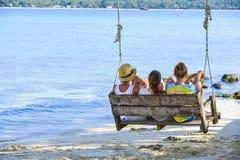 Eine Gruppe des Reisenden sitzend auf hölzernem Schwingen auf KohKham-Insel stockbild