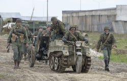 Eine Gruppe deutsche Soldaten mit dem Traktor SdKfz 2 und Panzerabwehr- Gewehre, welche die Straße weitergehen Rekonstruktion der Stockfotografie